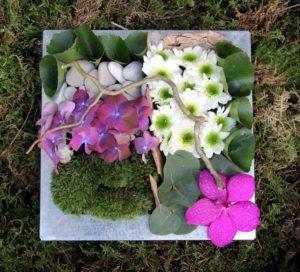 Composition fleurs piquées dans la mousse dans un plateau métallique