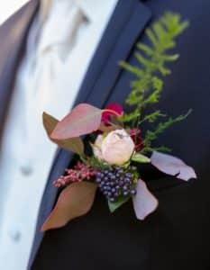Boutonière du mariée avec rose pastel, asparagus, ecaliptus, baies rouges et violette foncée