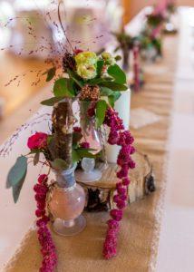 Chemin de table avec petit vase en verre, rondin de bouleau et végétaux : amarante rose branchue blanche, eucalptus, graminée rouge su un tissus de lin