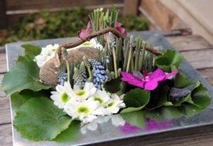 Composition fleurs piquées dans la mousse muscaris orchidées germini.