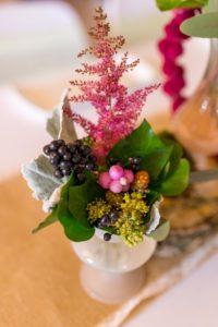 Petit vase pour chemin de table contenant du feuillage, des baies roses et noirs et une graminée rose
