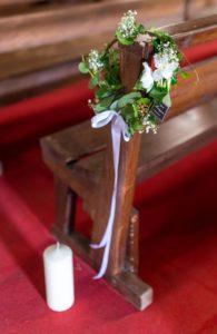 Petite couronne végétative poiur décoration de banc d'église avec gypsophile et fleurs blanche. Bougie au pied du banc.