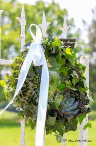 Couronne végétative avec baies , lierre et echeveria ornementée d'un ruban