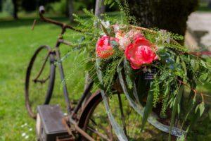 Composition de pivoine corail de rose pastel et de graminées dans une corbeille en osier sur un vieux vélo
