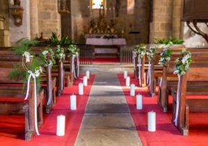 Décoration des bancs d'église avec couronne végétative verte et blanche plus bougie