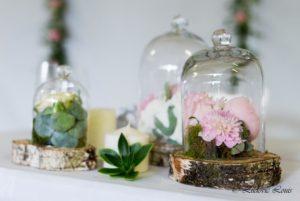 Décoration de table de mariage avec pivoines roses sous cloches et rondins de bois