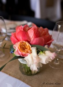 Petit centre de table constituée de pivoine corail de rose pastel et de pois de senteur dans un bocal en verre