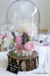 Des roses et des pivoines blanches sous cloche et des rondins de bois pour une décoration de mariage romantique