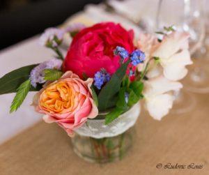 Petit centre de table constituée de pivoine corail de rose pastel et de pois de senteur et de bleuet dans un bocal en verre