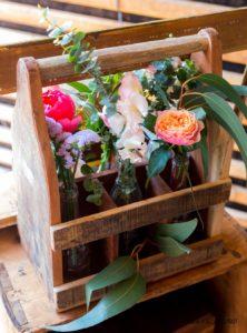 Décoration floral d'un ancien casier à bouteille en bois avec de l'eucaliptus des rose saumon et des pivoine corail