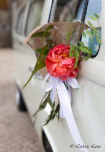 Décoration de poignée d'une voiture de mariée avec pivoine corail et graminée et ruban blanc