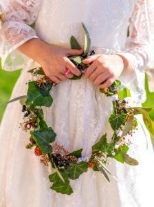 Couronne végétative de demoiselle d'honneur avec lierre, eucaliptus, gypsophile, mures et baies noires portée entre les mains d'une petite filles